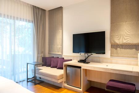 Innenliegendes Hotelzimmer mit LED-Fernseher und Jalousien