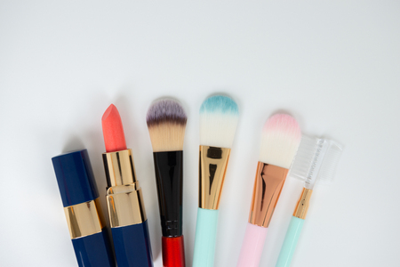 Flat lay creative concept of female decorative cosmetic for brush on and lipstick on the white background with copy space