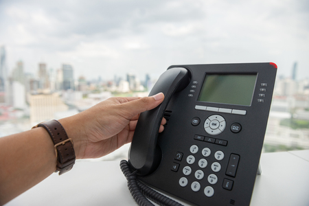 Man hand is holding the IP Phone handset to receive a call