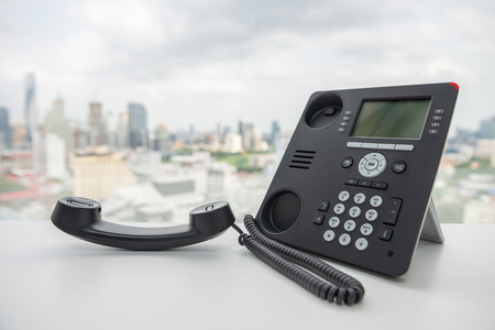 Black IP Phone on the white table with city scape background