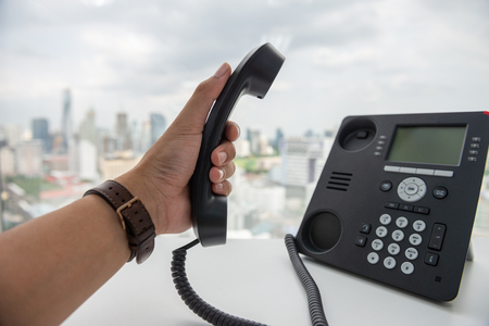 Man hand is holding the IP Phone handset