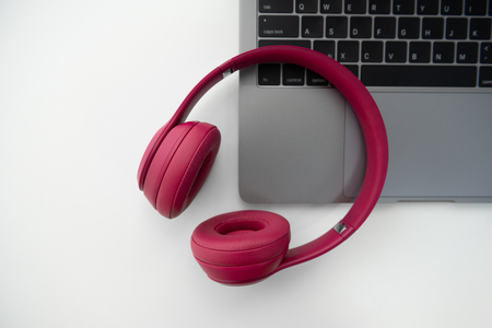 Flay lay of pink wireless headphone on the laptop keyboard Standard-Bild - 106658909