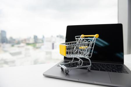 Mini shopping cart model on the laptop for online shopping concept Standard-Bild - 106658911