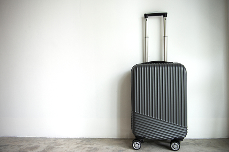 Black luggage trolley wheel on the white wall with copy space Standard-Bild - 106658945