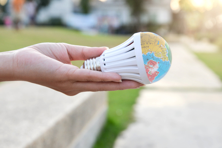 Hand is holding the LED bulb with nature background for save the earth concept Standard-Bild - 118981070