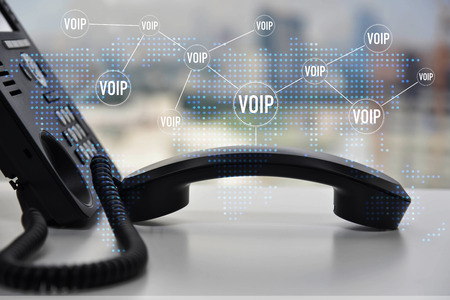IP Phone double exposure with blue LED world map and business icon of VOIP for communication concept