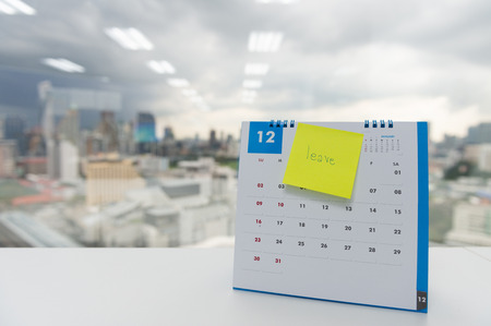Leave on paper note stick on the calendar of December for year end holidays concept