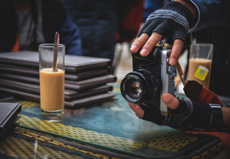 Photographer hand is holding the vintage camera to taking photo Standard-Bild - 118982041