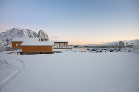 Yellow fishing rorbuer builded from wood and scaffolding dried fish in Reine village with beautiful sky at Lofoten Norway Фото со стока