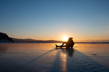 Silhouette photo of happy woman is sit and kiss the sun on ice