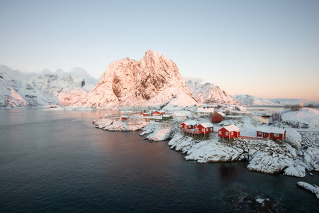 Red fishing house village among the snow with mountain view in Lofoten island Hamnoy Norway