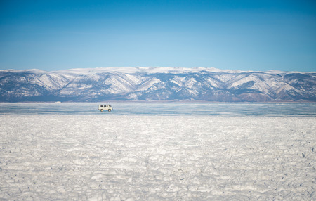Landscape of Frozen Lake Baikal with old van running on the ice road in the winter