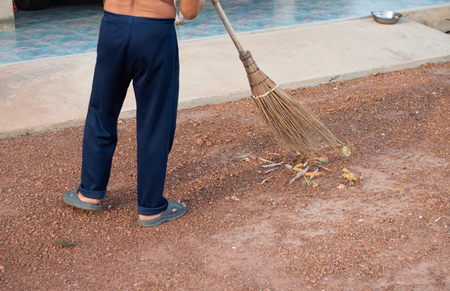 The man is sweeping the floor with the broom made from coconut leaves