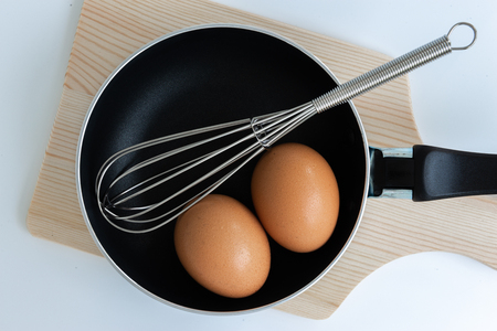 Close up pan with egg and stainless steel egg whisk and chopping on the white background
