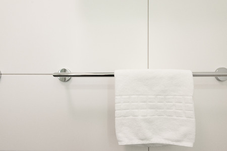 White towel hanging on the clothes rack in the bathroom in the hotel Banco de Imagens