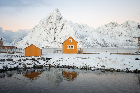 Yellow fishing rorbuer builded from wood on the white snow of winter with mountain view on the background in Reine village at Lofoten Norway Banco de Imagens