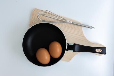 Pan with egg and stainless steel egg whisk and chopping on the white background Banco de Imagens
