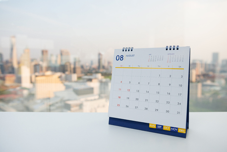Calendar of August on the white table with city view background