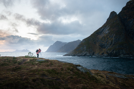 Landscape : woman is taking a photo with the camera and tripod at the fjord in Lofoten Norway