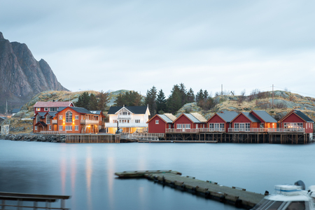 Long exposure of dock with fishing rorbuer house village in Lofoten island Hamnoy Norway