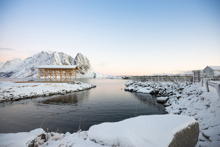 Landscape Scaffolding dried fish site of the sea bay on fully snow and beautiful sky in Reine at Lofoten Norway Banco de Imagens