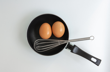Pan with egg and stainless steel egg whisk on the white background