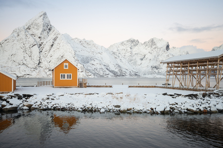Landscape of little yellow house with scaffolding dried fish site of the sea bay on fully snow and beautiful sky in Reine at Lofoten Norway Banco de Imagens
