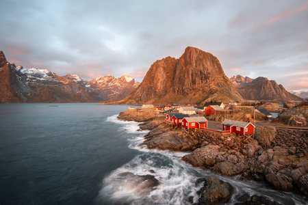 Long exposure of red fishing rorbuer house village with sunrise light and mountain view in Lofoten island Hamnoy Norway