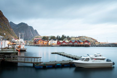 Long exposure of dock with speed boat and fishing rorbuer house village in Lofoten island Hamnoy Norway