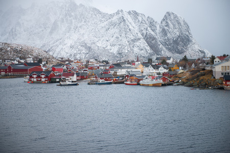 Fishing house village among the snow with mountain view in Lofoten island Reine Norway Imagens