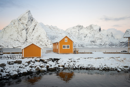 Yellow fishing rorbuer builded from wood on the white snow of winter with mountain view on the background in Reine village at Lofoten Norway Banco de Imagens - 121552509