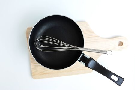 Pan and stainless steel egg whisk and chopping on the white background  Фото со стока
