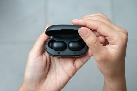 Close up of woman is open the black true wireless earbuds case Stock Photo