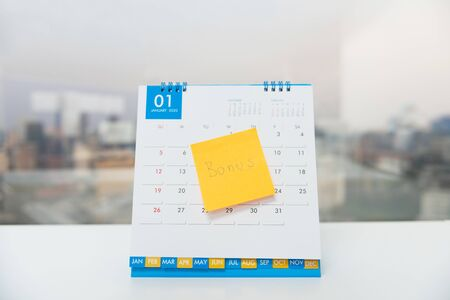 Paper post with Bonus wording stick on the calendar of January for business benefit concept