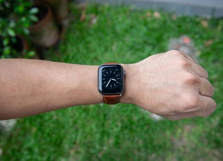Modern smart watch with leather strap on the man hand  and lighting of sun lay Reklamní fotografie