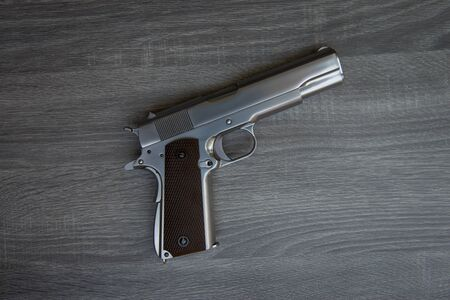 Stainless hand gun with brown hand grip is on the wooden floor