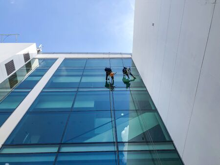 Cleaning staff using the rope to abseil from the building to wipe the glass