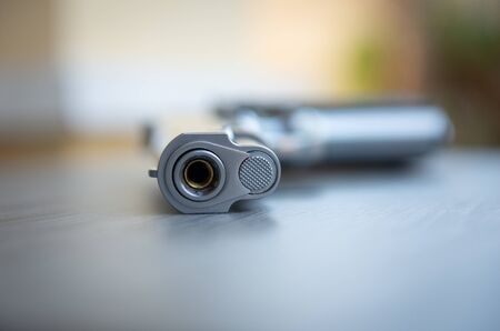 Close up of gun barrel on the wooden table