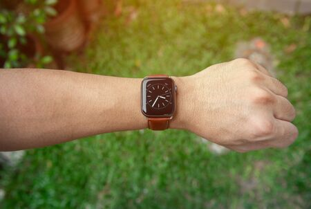 Modern smart watch with leather strap on the man hand