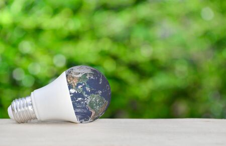 LED bulb as a globe on wooden table with green nature background for eco saving concept.
