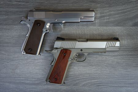 Two stainless hand guns with brown hand grip is on the wooden floor