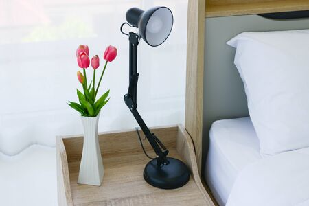 Close up of modern bed and bedside cabinet with flower vase in the bedroom