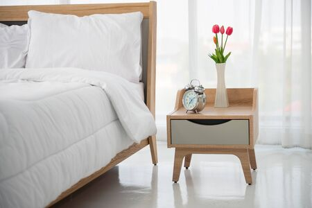 Close up of modern bed and bedside cabinet with clock and flower vase in the bedroom