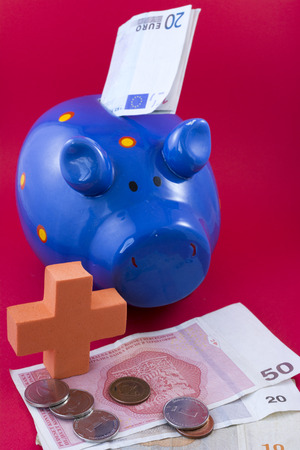 safeness: Photographed ceramic piggy bank with banknotes on a red background. Stock Photo