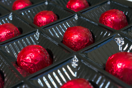 glint: Photographed chocolates wrapped in red foil.