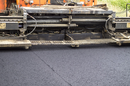 paver: Asphalt paver machine during road construction and repairing works. Stock Photo