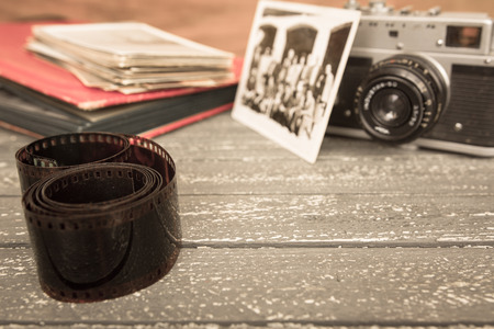 Old film and camera on a wooden background.
