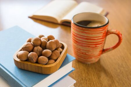 Relaxing reading books with coffee and hazelnuts.