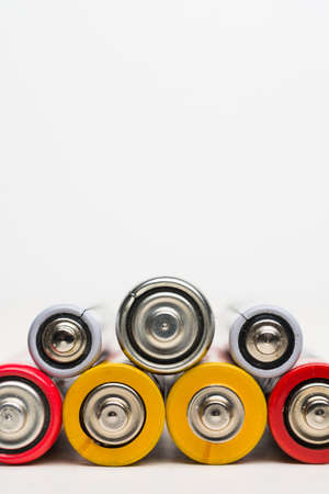 Spent batteries stacked in a row isolated on a white background.