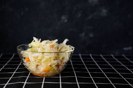 glass bowl with homemade sauerkraut, cranberries, on a dark background. Made from cabbage and carrots. On the black tablecloth with copyspace